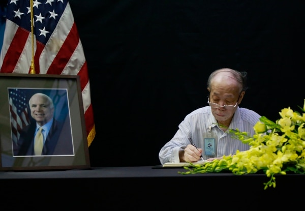 Pham Minh Chuc, an 81-year-old retiree, writes in a book of condolences for Sen. John McCain in Hanoi, Vietnam on Monday, Aug. 27, 2018. People in Vietnam are paying their respects to Sen. John McCain, who was held as a prisoner of war in Vietnam and later was instrumental in bringing the wartime foes together. McCain died on Saturday, Aug. 25. (AP Photo/Tran Van Minh)