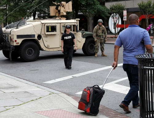 A man walks through an intersection blocked by a military Humvee from D.C. National Guard and a DEA police officer as demonstrators gather to protest the death of George Floyd, Tuesday, June 2, 2020, in Washington. Floyd died after being restrained by Minneapolis police officers. (Jacquelyn Martin/AP)