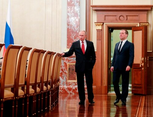 Russian President Vladimir Putin, right, and Russian Prime Minister Dmitry Medvedev talk to each other prior to a Wednesday cabinet meeting in Moscow. The Tass news agency reported that Medvedev submitted his resignation to President Vladimir Putin. (Dmitry Astakhov, Sputnik, Government Pool Photo via AP)