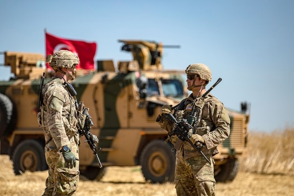 U.S. soldiers chat next to a Turkish military vehicle during a joint patrol with Turkish troops in the Syrian village of al-Hashisha on the outskirts of Tal Abyad town along the border with Turkish troops, on Sept. 8, 2019. (Delil Souleiman/AFP via Getty Images)