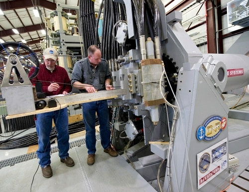 Gary Bass, left, and Jim Poyner, from the Naval Surface Warfare Center's Dahlgren Division, take measurements after a successful test firing of an electromagnetic railgun prototype launcher on Feb. 23, 2012. (John F. Williams/U.S. Navy via AP)