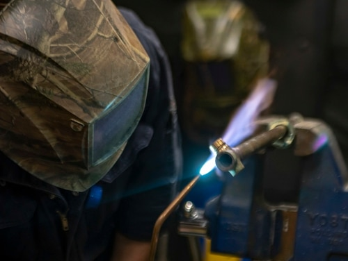 Hull Maintenance Technician 3rd Class Zachary Yenco welds a pipe fitting aboard the amphibious assault ship Essex while it sailed the Gulf of Aden on Sept. 5. Navy reforms promise to let hull techs take advantage of career advancement in similar fields such as damage control. (MC3 Molly DiServio/Navy)