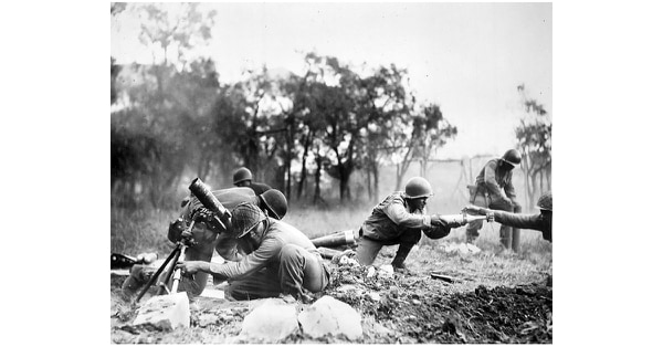 Members of a mortar company of the 92nd Division pass the ammunition and heave it over at the Germans in an almost endless stream near Massa, Italy. This company is credited with liquidating several machine gun nests. November 1944. (U.S. Army)