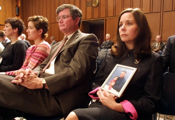 Connie Gruber, right, widow of co-pilot Maj. Brooks Gruber, holds a photo of her husband and their daughter, Brooke, as she listens at a hearing before the Senate Armed Services Committee in 2001. (Alex Wong/Getty Images)