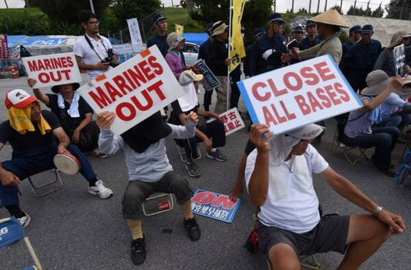 People hold up placards as they protest against the presence of US bases, in front of the gate of the US Marine Corps' Camp Schwab in Nago on the southern island of Okinawa prefecture on June 17, 2016. Okinawans are planning a major rally on June 19 in protest over the heavy US military presence and crimes by US personnel. / AFP / TORU YAMANAKA (Photo credit should read TORU YAMANAKA/AFP/Getty Images)