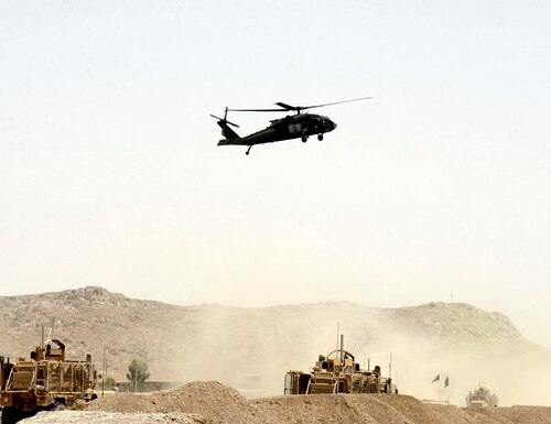 A U.S. helicopter flies over the site of a suicide bomb that struck a NATO convoy in Kandahar south of Kabul, Afghanistan, Aug. 2, 2017. (AP)