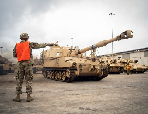 An infantryman with 2nd Brigade Combat Team, 3rd Infantry Division guides vehicles at the port of Savannah, Ga., in preparation for DEFENDER-Europe 20 Feb. 11, 2020. (Pfc. Nathaniel Gayle/Army)