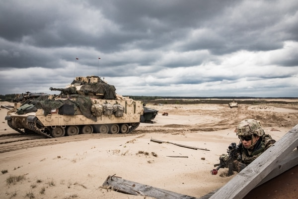 A U.S. infantryman with the 1st Infantry Division pulls security next to an M2 Bradley Fighting Vehicle on a range in Trzebień, Poland during a simulated training exercise, May 14, 2019. (Sgt. Jeremiah Woods/Army)
