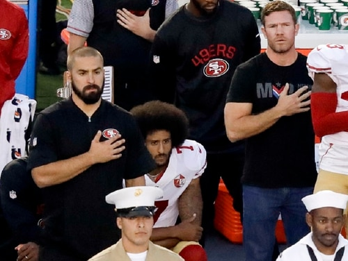 Army veteran Nate Boyer stands to the right of San Francisco 49ers quarterback Colin Kaepernick, middle, before a Sept. 1, 2016, preseason game in San Diego. The NFL's new policy on the national anthem was revealed nearly two years after Kaepernick's initial protest. (Chris Carlson/AP)