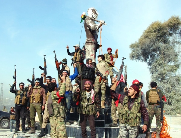 Turkey-backed Free Syrian Army soldiers celebrate around a statue of Kawa, a mythology figure in Kurdish culture as they prepare to destroy it in city center of Afrin, northwestern Syria, early Sunday, March 18, 2018. (Hasan Kırmızitaş/DHA-Depo Photos via AP)