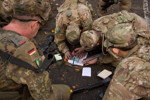 A team of soldiers from 2d Cavalry Regiment and a Panzer Brigade from the German Army plot a point on a map for a land navigation event during a cavalry spur ride Nov. 2, 2017, in the Grafenwoehr Training Area, Germany. (Staff Sgt. Jennifer Bunn/Army)