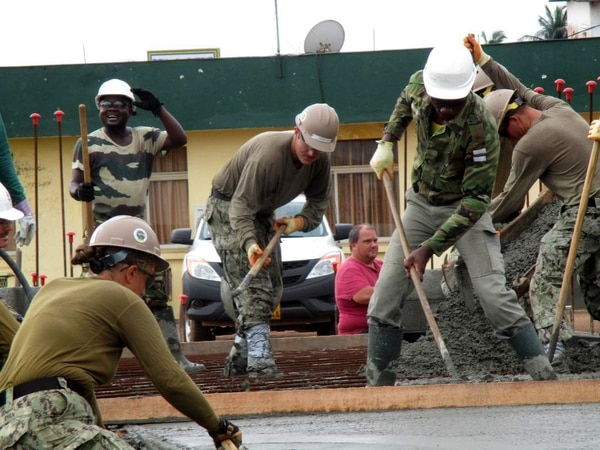 Seabees assigned to Naval Mobile Construction Battalion 1 work with the Gabonese Genie military to move concrete during construction of the Maritime Operations Center at the Gabonese Navy Base on Nov. 19 in Port Gentil. (Utilitiesman 2nd Class Krista Sosa/Navy)