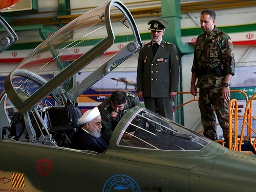 Iranian President Hassan Rouhani is briefed by an air force pilot as he sits in the cockpit of the Kowsar fighter jet at an inauguration ceremony of the aircraft on Aug. 21, 2018. Iran on Tuesday displayed a new twin-seat fighter jet it says is all Iranian-made and which allegedly has advanced avionics and fire control systems. Defense Minister Gen. Amir Hatami stands at second right. (Iranian Presidency Office via AP)