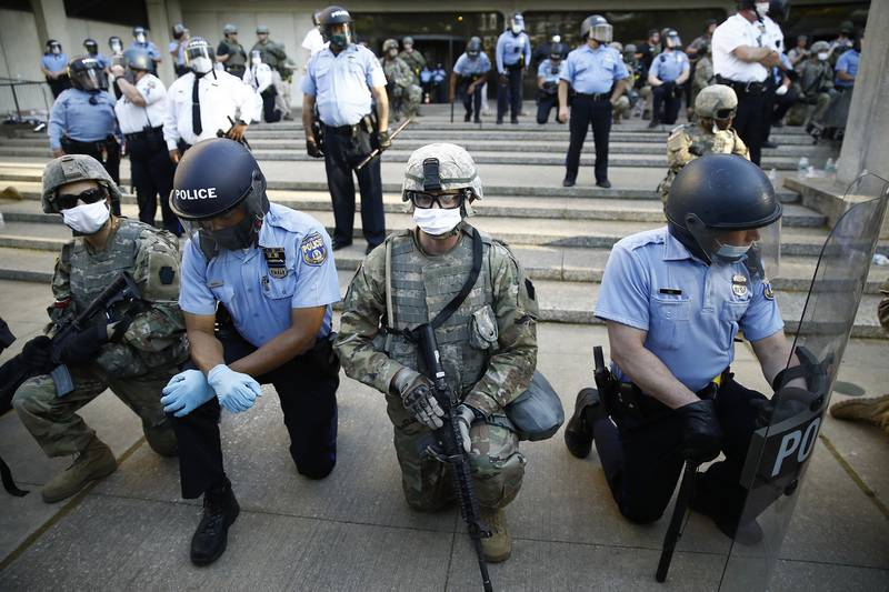 In this June 1, 2020, file photo, Philadelphia police and Pennsylvania National Guard take a knee at the suggestion of Philadelphia Police Deputy Commissioner Melvin Singleton, unseen, outside Philadelphia Police headquarters in Philadelphia, during a march calling for justice over the death of George Floyd.
