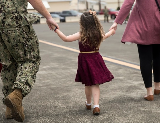 A U.S. sailor and his wife walk together while holding the hands of their daughter during a homecoming, April 2018. A stop-movement order is delaying redeployments for many units. (Sgt. Alex Kouns/Marine Corps)