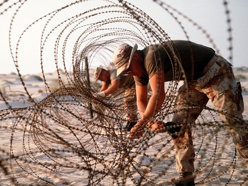 FILE PHOTO: U.S. Marines deploy concertina wire to prevent infiltration of their encampment during Operation Desert Shield. (photo by DOD)
