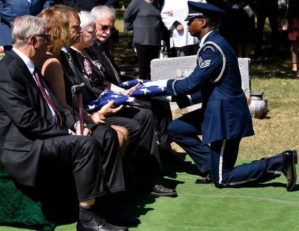 Gayanne Knight receives a folded U.S. flag from a U.S. Air Force honor guard member during the burial service for her father, Col. Roy Knight Jr., Saturday, Aug. 10, 2019 in Cool, Texas. Beside her are her brothers, Bryan and Roy Knight III, who also received flags. (Ronald W. Erdrich/The Abilene Reporter-News via AP)