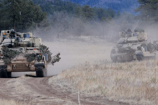 Soldiers drive their M3A3 Bradley Fighting Vehicles to reach a phase line where they will move into a defensive posture during platoon scout training. (Staff Sgt. Andrew Porch/Army)