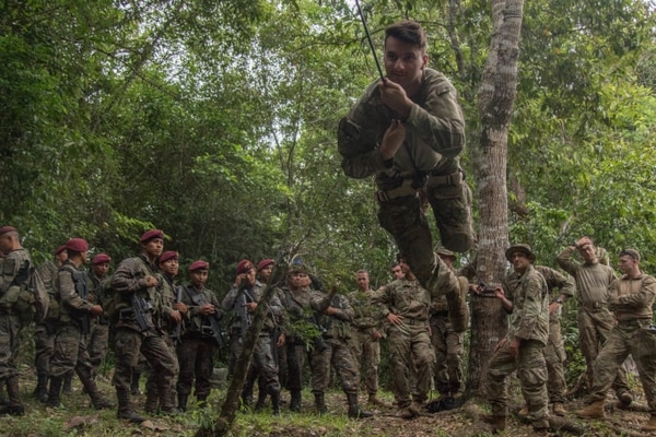 A U.S. Army sergeant combat crawls across a rope bridge as Guatemalan special forces watch on July 17, 2019. (Army)