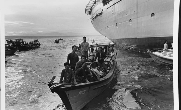Boatloads of refugees from the Phan Rang area approach the amphibious cargo ship Durham for transfer to a safer area on April 3, 1975. Note motorbikes in this boat. (National Archives)