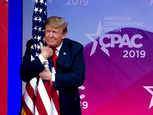 President Donald Trump hugs the American flag as he arrives to speak at Conservative Political Action Conference in Oxon Hill, Md., on March 2, 2019. During his speech, Trump claimed to have come up with former Defense Secretary Jim Mattis' nickname of
