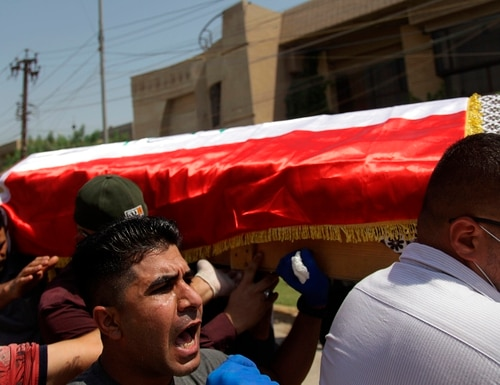 Mourners carry the flag-draped coffin of Hisham al-Hashimi during his funeral, in the Zeyouneh area of Baghdad on July, 7, 2020. Al-Hashimi, an Iraqi analyst who was a leading expert on the Islamic State and other armed groups, was shot dead in Baghdad on Monday. (Khalid Mohammed/AP)