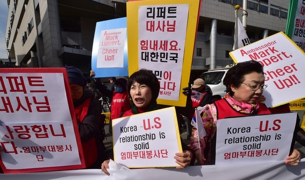 South Korean women supporting the US hold placard reading