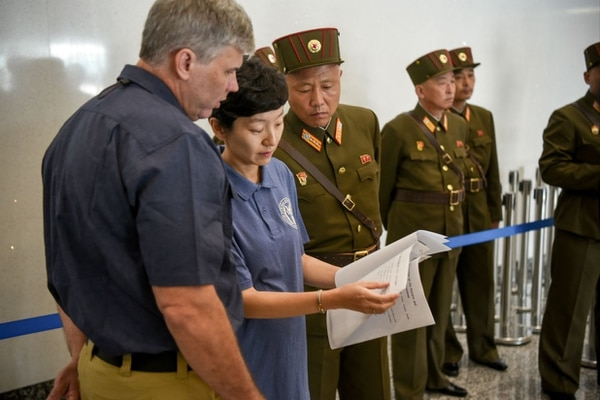 Defense POW/MIA Accounting Agency lab director John Byrd and forensic anthropologist Jennie Jin traveled to North Korea in July to receive 55 boxes of remains from the Korean War. Above, they review a list of geographic descriptions provided with each box as North Korean officials look on. Byrd and Jin are now in the process of using DNA testing and other scientific methods to ID the remains. (Sgt. 1st Class David J. Marshall/Army)