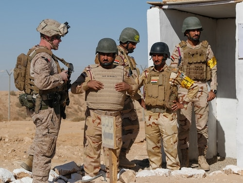 A U.S. Marine, left, speaks to Iraqi Security Forces forward observers before a live-fire artillery training event on Al Asad Air Base, Iraq, Oct. 30, 2018. (1st Lt. Leland White/Army National Guard)