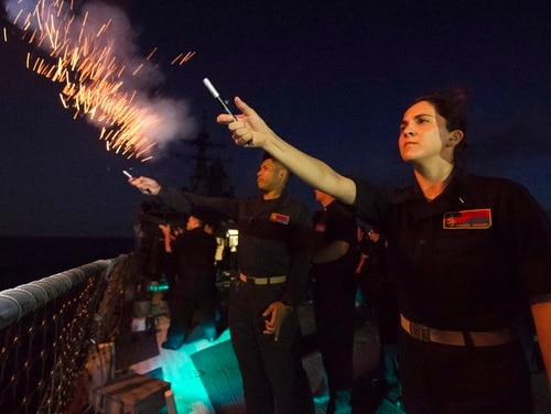 Then-Ensign Lauren Kearney, the strike officer aboard the guided-missile destroyer Benfold, fired pencil flares from the ship's fantail after a promotion ceremony on Memorial Day. Commanders promoted six officers to lieutenant junior grade while underway in the Philippine Sea. (MC2 Anna Van Nuys/Navy)