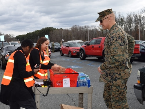 Col. William C. Bentley, III, Marine Corps Base Quantico commanding officer, reaches for his wallet as Quantico Commissary employees Shawna Reeves and Frederick Rogers finalize his Click2Go order in December, 2019. (Rick Brink/DeCA)