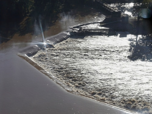 FILE -In this Oct. 6, 2015, file photo, floodwaters rush over a diversion dam in Columbia, S.C. The historic rains and floods that battered South Carolina last October destroyed more than $1 billion dollars in homes and property, and left thousands struggling to recoup. (AP Photo/Chuck Burton, File)