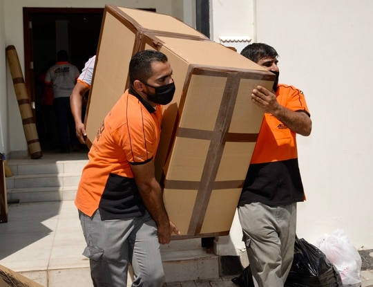 The services are working to increase weight allowances for military members. Here, moving company employees in Bahrain carry a heavy item to the truck during the a household goods move amid the COVID-19 crisis. (Kambra Blackmon/Navy)