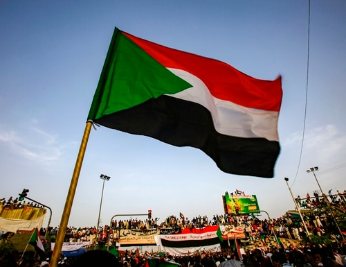 A Sudanese flag is seen waving as protesters chant slogans during a demonstration demanding a civilian body to lead the transition to democracy, outside the Army headquarters in the Sudanese capital Khartoum on April 12, 2019. (Ashraf Shazly/AFP via Getty Images)