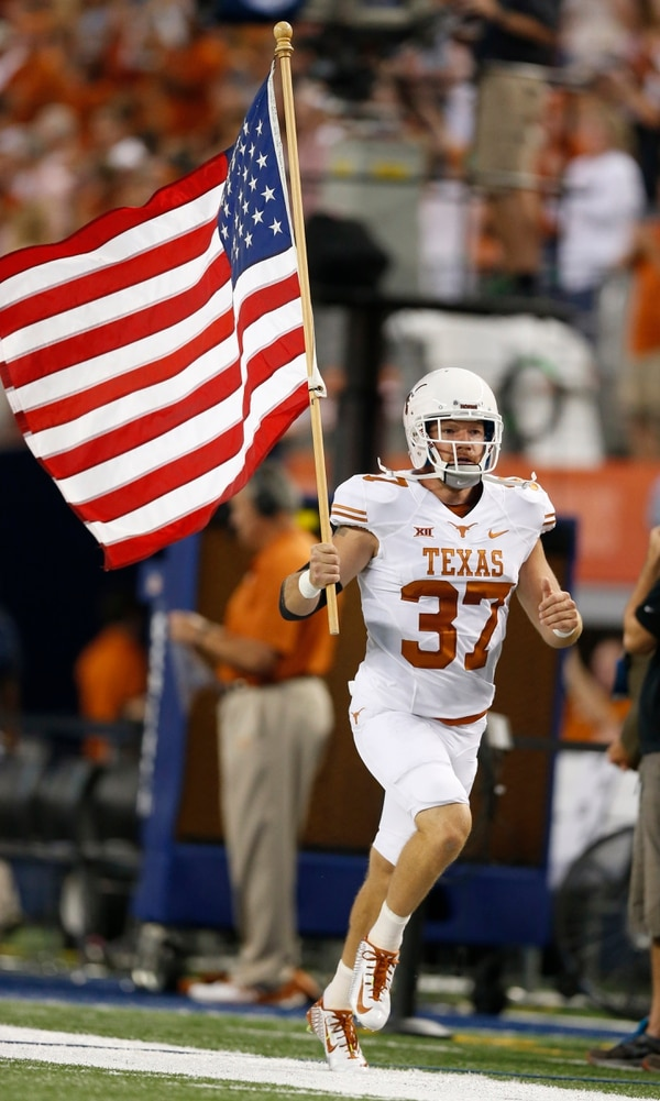 Texas Longhorns long snapper Nate Boyer carries the American flag prior to a game against UCLA at AT&T Stadium in Arlington, Texas, home of the Dallas Cowboys. (Matthew Emmons/USA Today Sports)