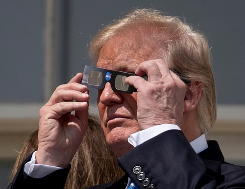 President Donald Trump puts on protective glasses to view the solar eclipse at the White House. (Andrew Harnik/AP)
