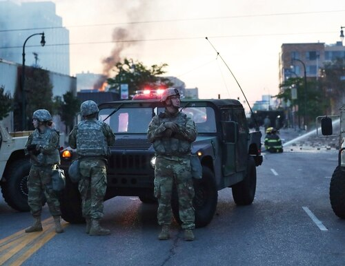 Minnesota National Guard members maintain a position protecting nearby firefighters in the wake of the death of George Floyd while in police custody earlier in the week and seen Saturday, May 30, 2020, in Minneapolis. (David Joles/Star Tribune via AP)