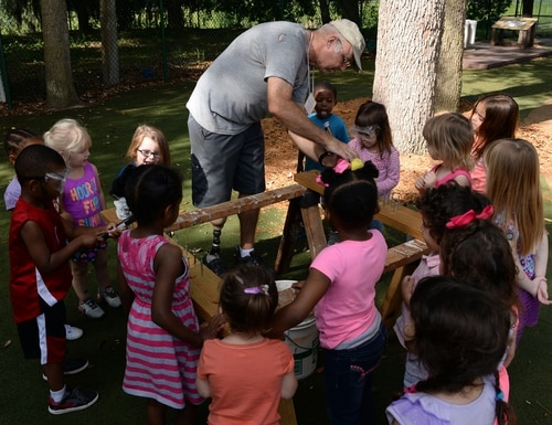 Machinery Repairman 1st Class (retired) Harley Herndon teaches children at Mayport Child Development Center (CDC) how to hammer nails into wood during woodworking day, April 21, 2015, in Florida. There will be fewer visitors at CDCs as installations grapple with a global coronavirus pandemic. (Mass Communication Specialist 3rd Class Mark Andrew Hays/Navy)