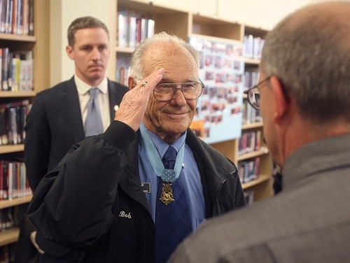 In this Nov. 8, 2013, file photo, Medal of Honor recipient Bob Maxwell, center, salutes at a ceremony at Bend High School in Bend, Ore., where he received a commemorative set of postage stamps honoring the few surviving Medal of Honor recipients from World War II. (Andy Tullis/The Bulletin via AP, File)