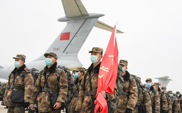 Chinese military medical staff members stand in formation after arriving at Wuhan Tianhe International Airport in Wuhan in central China's Hubei Province, on Sunday. (Cheng Min/Xinhua via AP)