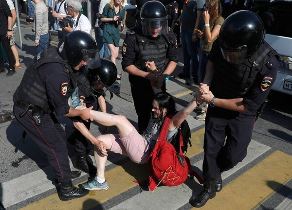 Police officers detain a woman during an unsanctioned rally in the center of Moscow on July 27. (Pavel Golovkin/AP)