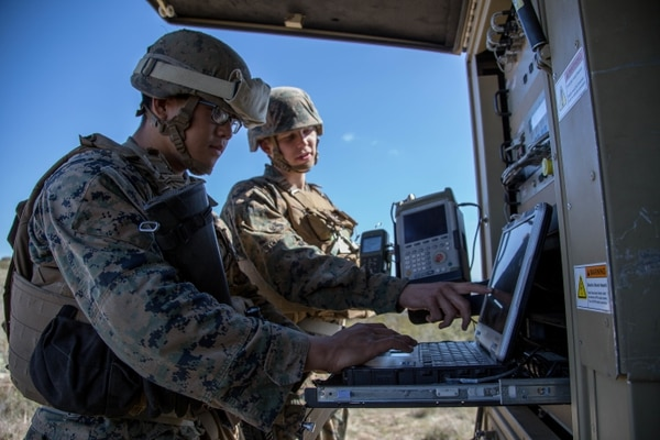 U.S. Marines Cpl. David Chung, left, and Lance Cpl. Bryce Moldovan, right, field radio operators with Headquarters Regiment, 1st Marine Logistics Group, work with a Very Small Aperture Terminal-Large antenna during a field exercise at Camp Pendleton, California, March 1. (Staff Sgt. Rubin J. Tan/Marine Corps)