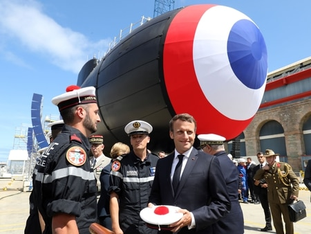 French President Emmanuel Macron, center, meets with submarine crew members after the official launch ceremony of the new French nuclear submarine Suffren in Cherbourg, northwestern France, on July 12, 2019. (Ludovic Marin/AFP via Getty Images)