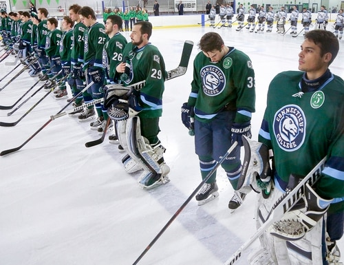 In this Feb. 6, 2016 photo provided by Connecticut College, the men's hockey team lines for a game against Tufts, wearing a special patch to mark the fifth annual Green Dot hockey game, on the campus in New London, Conn. The U.S. Air Force visited the college in March to get an up-close look at a school that has been using the Green Dot program to stem sexual assault, a problem that has been the target of crackdowns in recent years in higher education and the armed forces. The Air Force is introducing the program at all installations across the service. (Bob MacDonnell/Connecticut College via AP) MANDATORY CREDIT