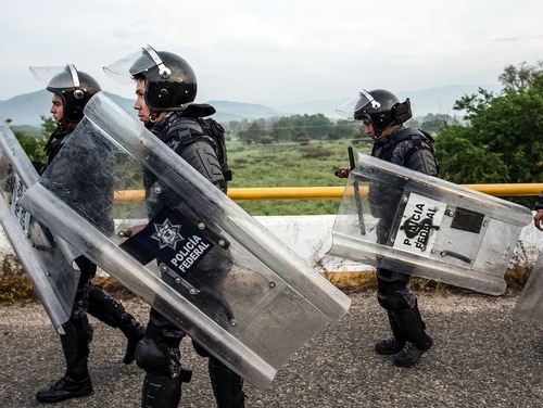 Mexican Federal Police officers unblock the road that Honduran migrants taking part in a caravan heading to the US on Oct. 27, 2018. The U.S. military is moving some equipment to the U.S.-Mexico border ahead of its response to a caravan of migrants headed there.(Guillermo Arias/AFP via Getty Images)