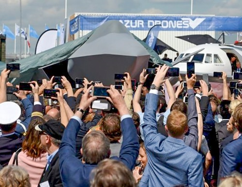 Visitors attend the unveiling ceremony of the full-scale jet fighter model of the French-German-Spanish new-generation Future Combat Air System during the 53rd International Paris Air Show on June 17, 2019. (Eric Piermont/AFP via Getty Images)