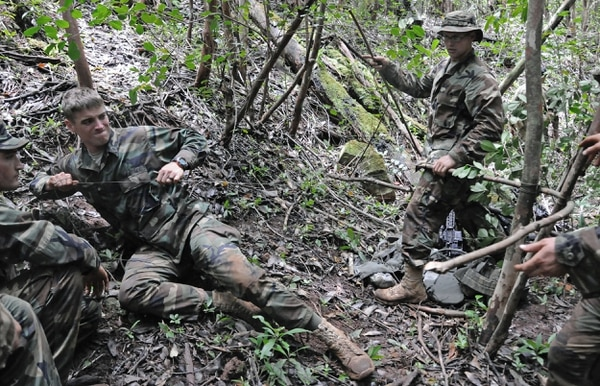 Students in the jungle warfare course at the Jungle Operations Training Center in Hawaii work to create a booby trap out of items found in the jungle. The Army is testing a new fabric for uniforms that are more suited to operating in the jungle. (Army)
