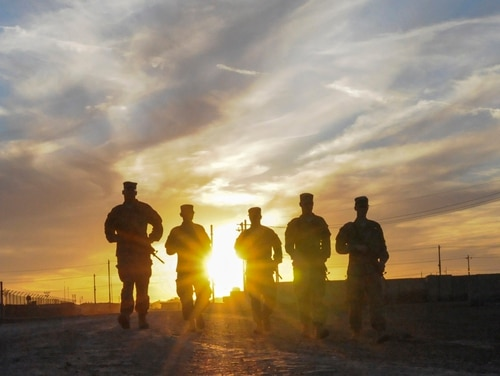 A group of U.S. soldiers walks along the road at sunset in Taji, Iraq, in March 2016. Pentagon officials issued new guidance this week for how to handle discharge upgrades for individuals who may have been dismissed because of undiagnosed medical issues. (Staff Sgt. Victor Joecks/Army National Guard)