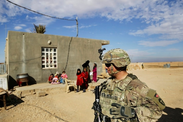 In this Jan. 27, 2018, photo, U.S. Army soldiers speak to families in rural Anbar on a reconnaissance patrol near a coalition outpost in western Iraq. (Susannah George/AP)