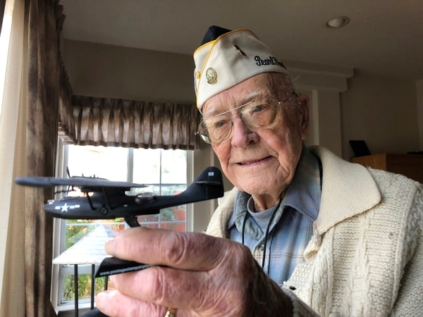 On Friday, Dec. 7, 2018, retired U.S. Navy Cmdr. Don Long holds up a replica of the military seaplane he was standing watch on when Japanese warplanes attacked Hawaii 77 years ago. Long was alone on the anchored plane in the middle of Kaneohe Bay, across the island from Pearl Harbor, when the attack happened, watching as the bombs and bullets killed and wounded thousands. When the gunfire reached his plane, setting the aircraft ablaze, he jumped into the water and swam through flames to safety. (Eric Risberg/AP)